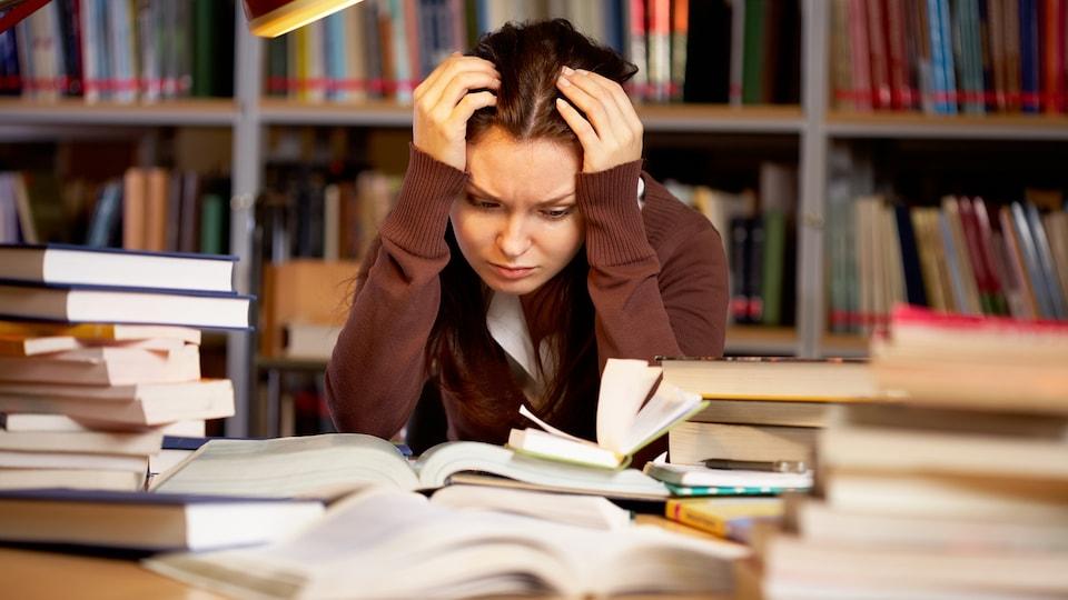 une étudiante découragée, devant ses livres