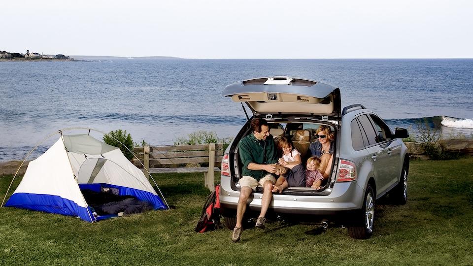 Une famille assise dans l'arrière d'un véhicule utilitaire sport sur le bord de l'océan.