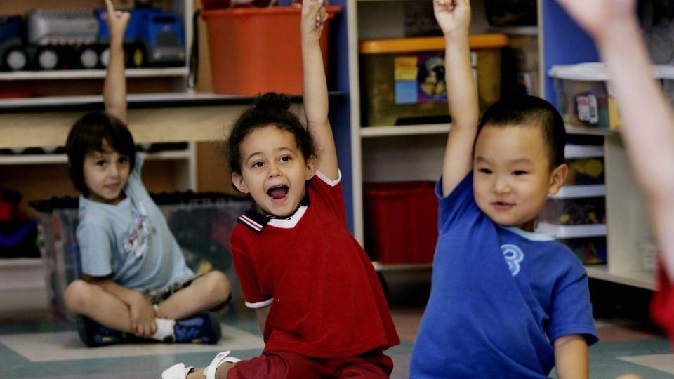Trois jeunes enfants de diverses nationalités sont assis au sol et lèvent leur main dans une salle de classe.