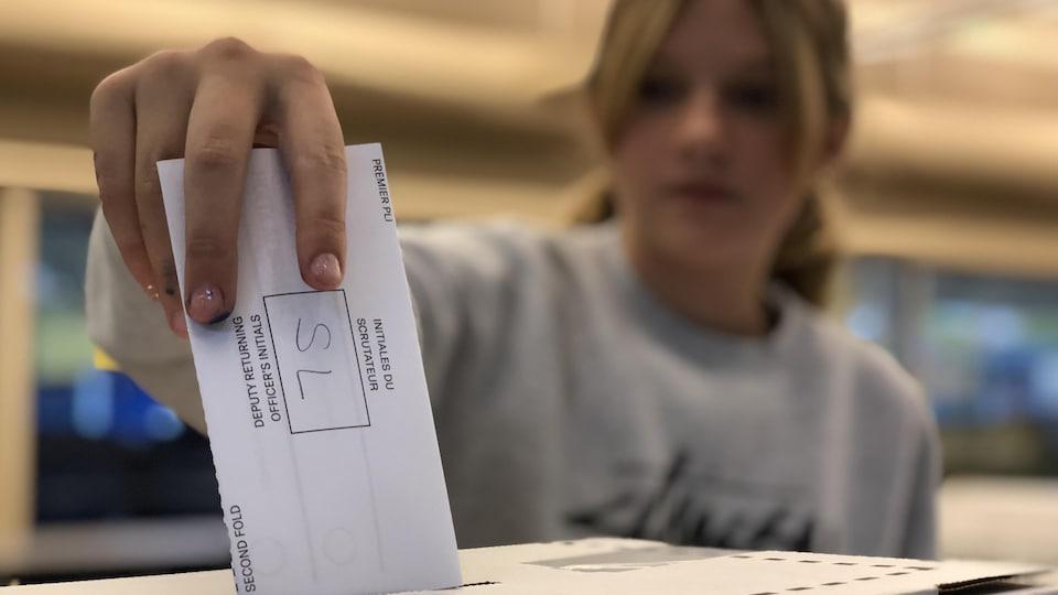 Une élève de l'école Gabrielle-Roy de Surrey ajoute son bulletin de vote à une boite de scrutin.