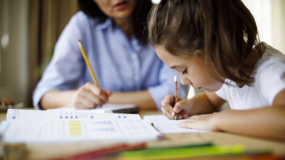 Une femme aidant un enfant à faire ses devoirs