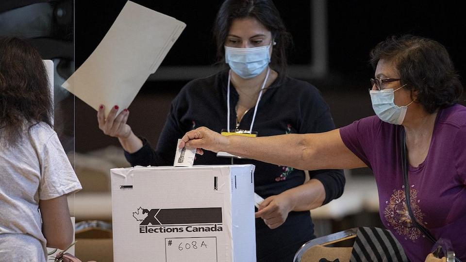 Une femme dépose son vote dans une boîte en carton.