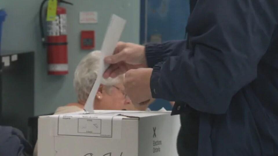Un homme glisse son bulletin de vote dans une urne.