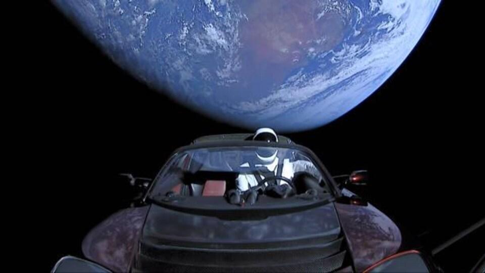 Une voiture décapotable avec un chauffeur factice devant la planète Terre.