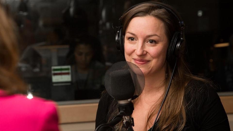 Une femme sourit devant un micro en regardant une personne en face d'elle.