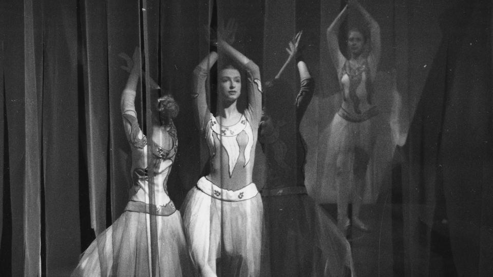 Trois ballerines derrière des rideaux vaporeux dansent les bras levés.