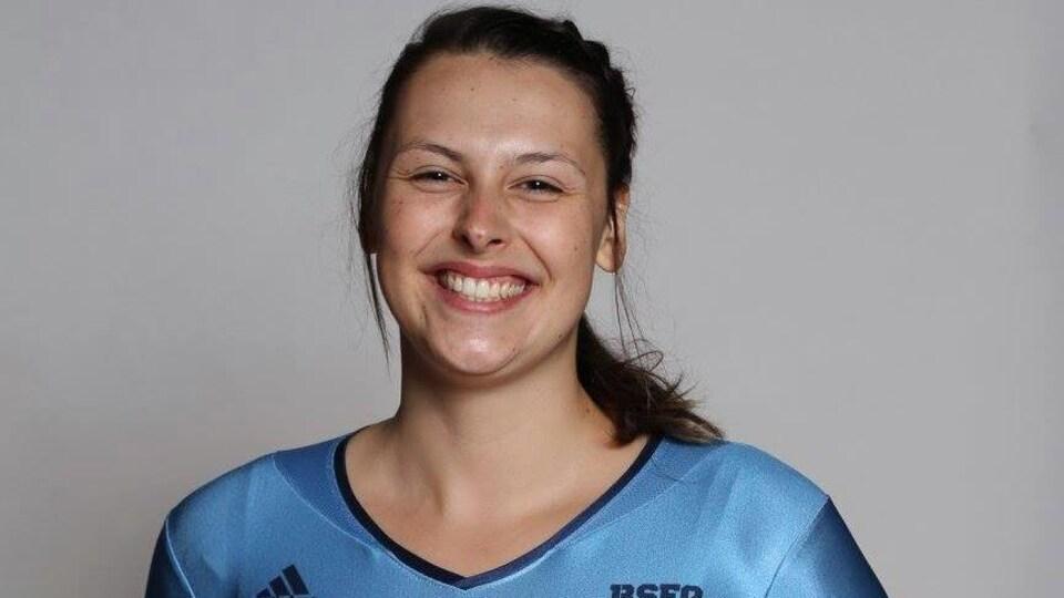 Une femme en combinaison sportive et souriant.