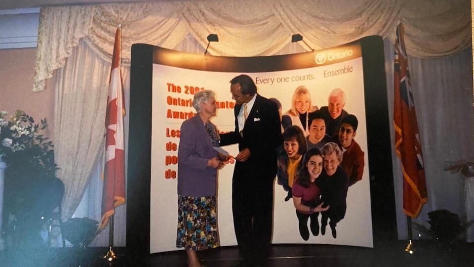 Une dame tenant un diplôme est accueillie par un homme sur une scène.