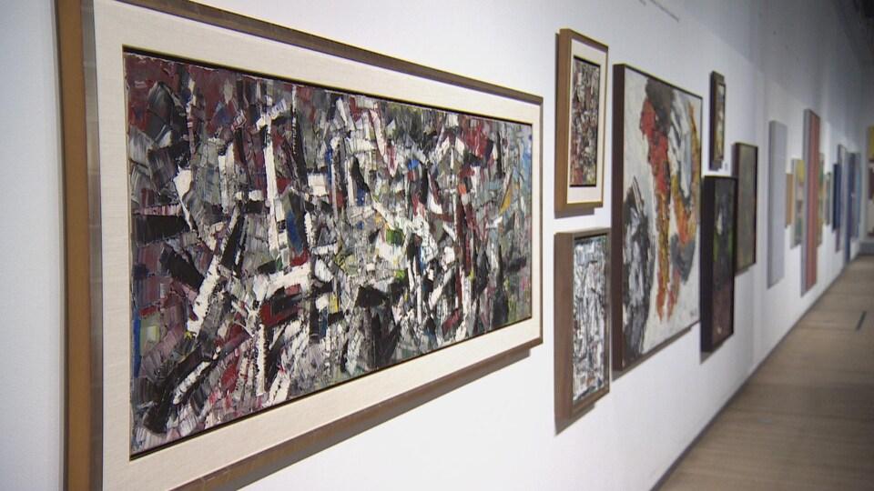 L'oeuvre de Riopelle est accrochée sur un mur blanc à proximité d'autres tableaux.