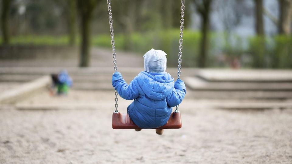 Un jeune enfant se balance dans un parc.