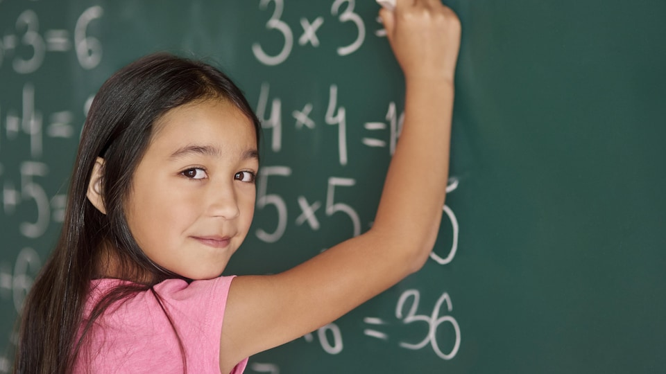 Une fille fait des calcules mathématiques à la craie blanche sur un tableau de classe vert.