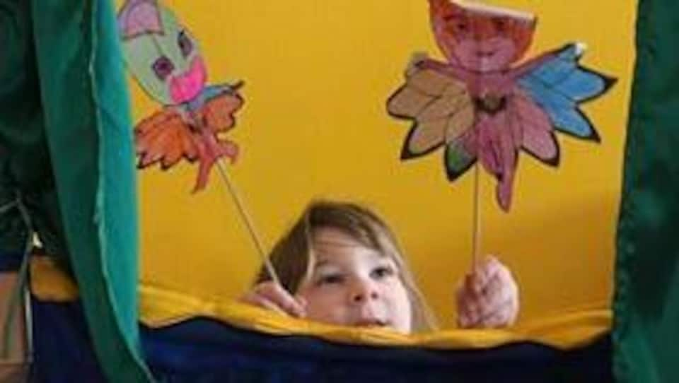 La petite fille d'Érika Soucy, s'amusant avec des marionnettes bricolées en papier.
