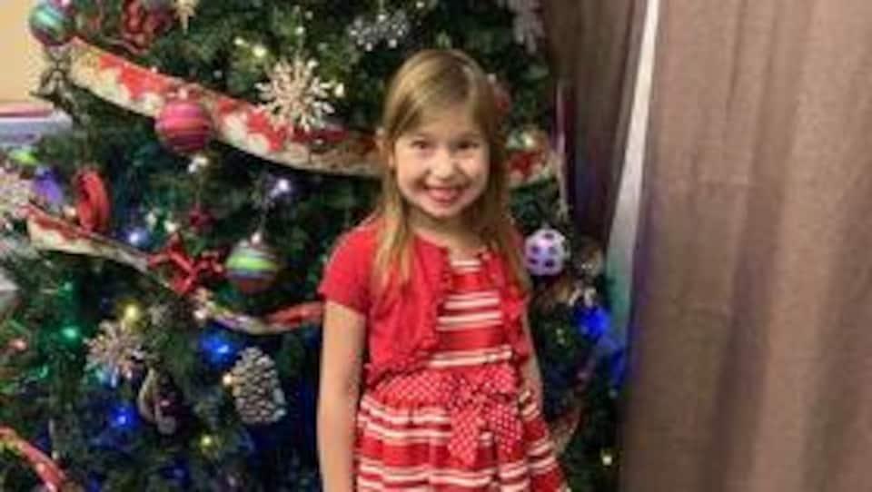 Une fillette au large sourire pose devant un sapin de Noël.