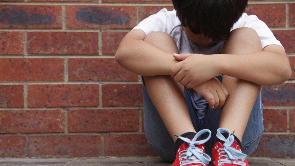 Un jeune garçon assis par terre et recourbé sur lui-même, la tête baissée.