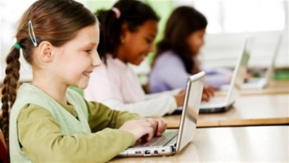 Des enfants sont assis devant des ordinateurs portables.