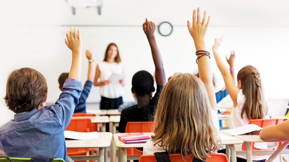 Des étudiants dans une classe lèvent la main pour poser une question au professeur.