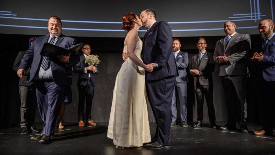Éric Veillette embrasse son épouse lors de son mariage célébré dans le cinéma Revue.