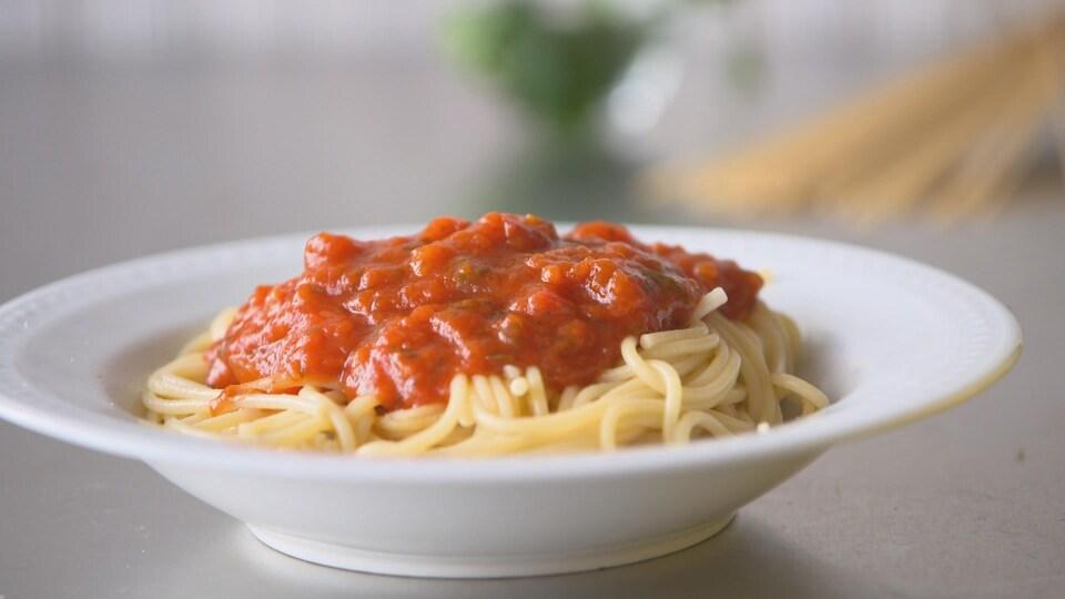 Une assiette creuse blanche remplie de spaghettis sauce tomate.