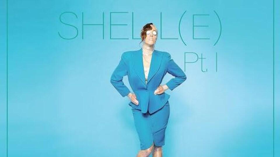 Marie-Clo habillé d'une veste et d'une jupe cigarette, debout, entourées de plusieurs verres et assiettes.
