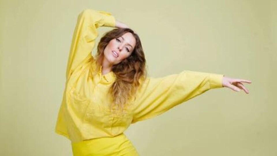 Marie-Clo dansant, les bras dans les airs, sur fond uni.