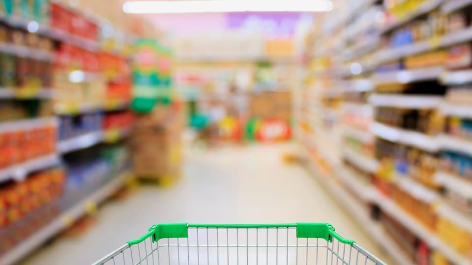 Un panier à roulettes dans une allée d'épicerie