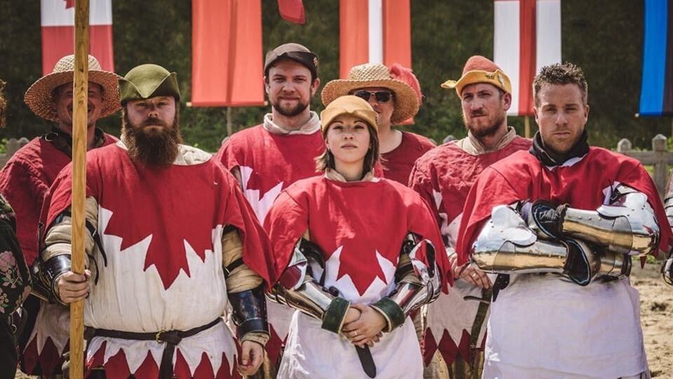 Des hommes et une femme qui portent une tunique médiévale blanche et rouge posent pour une photo