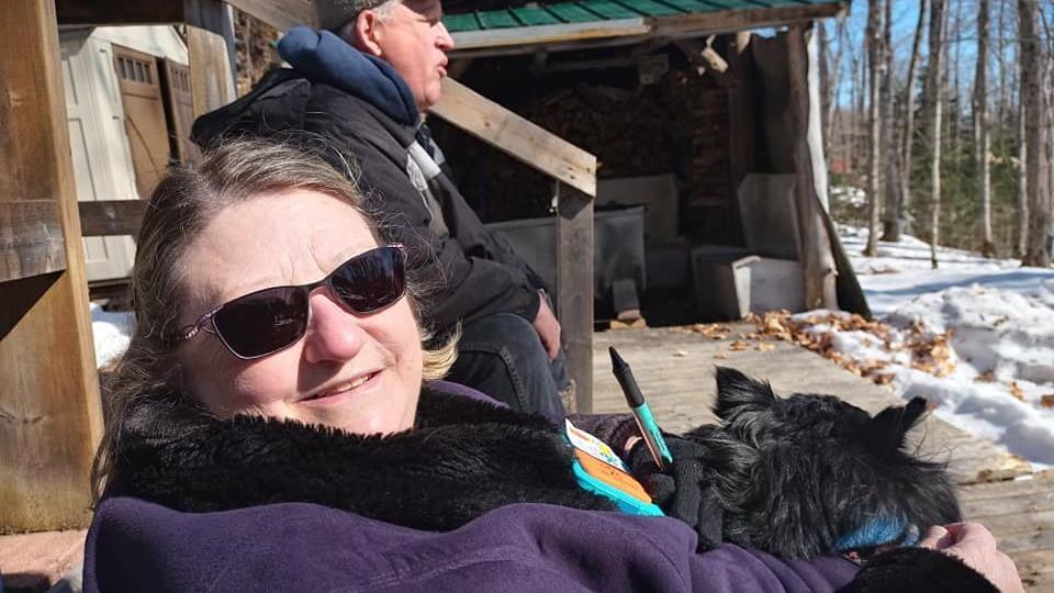 Couple et un chien dans leur structure d'ébullition de sève d'érable.