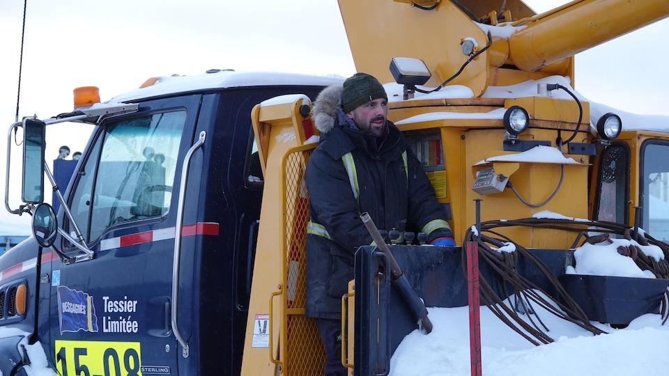 Éric Belley sur son camion en train de lever un énorme pneu