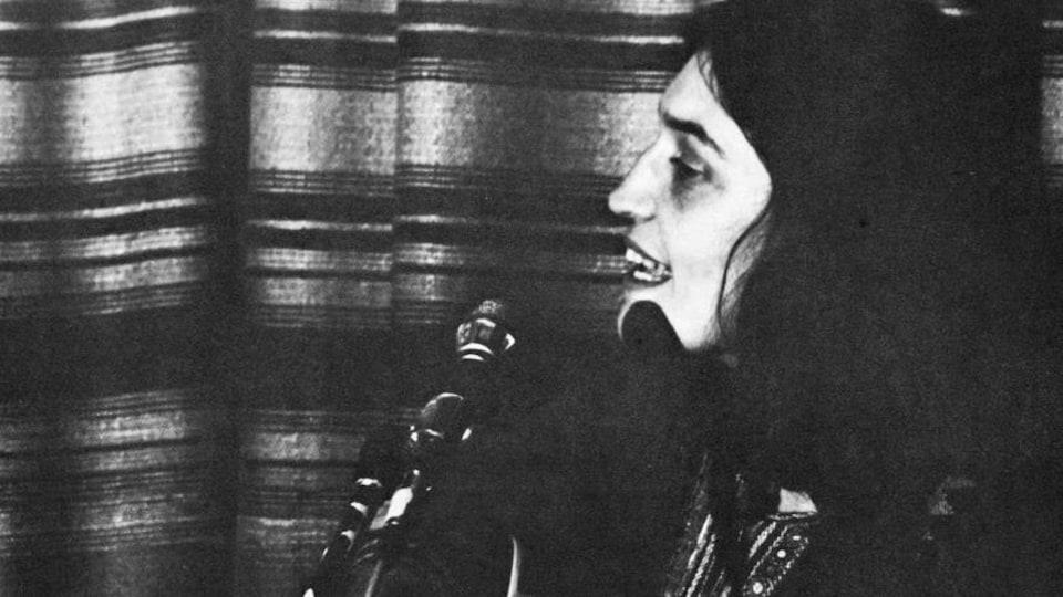 Elle chante guitare à la main.