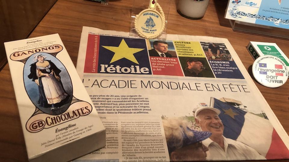Différents objets historiques acadiens exposés sur une table, dont une boîte de chocolat à l'effigie d'Évangéline, un exemplaire du journal l'étoile ainsi qu'un jeu de cartes de la Caisse Populaire acadienne.