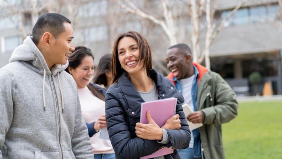 Cinq étudiants internationaux discutent en marchant sur un campus universitaire.