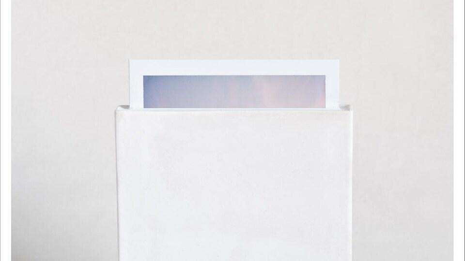 Une photo de type Polaroid prisonnière d'un moulage en plâtre; on ne voit que l'extrémité de la photo.