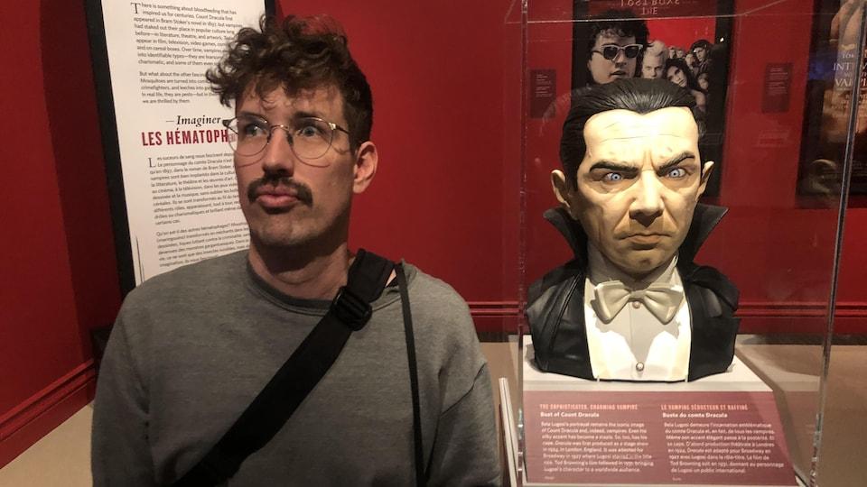 Olivier pose à côté du buste de Dracula le vampire dans l'exposition Soif de sang au Musée Royal de l'Ontario