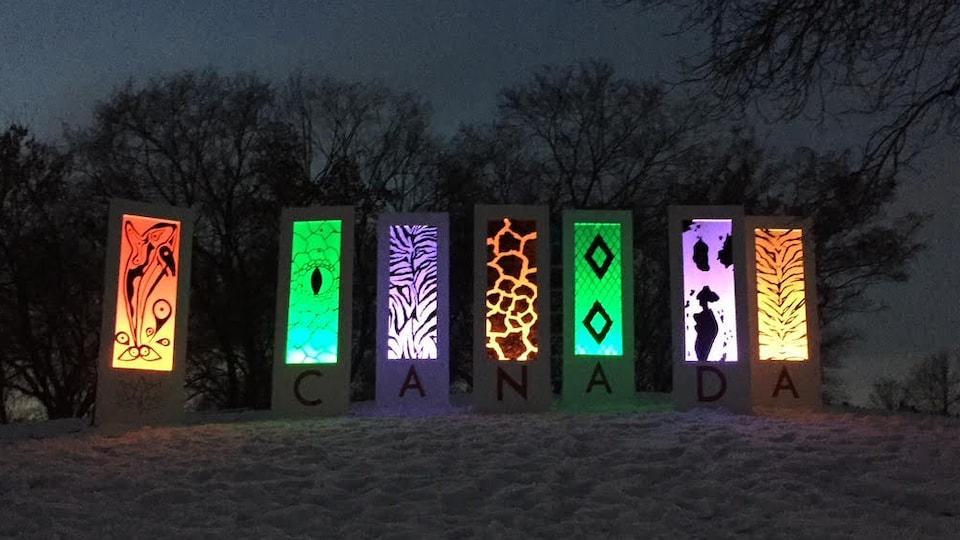 7 panneaux illuminés arborant 7 dessins distincts (épaulard, oeil, motif zébré, motif peau de girafe, écaille de serpent, peau de vache et peau de tigre) installés sur une colline enneigée.