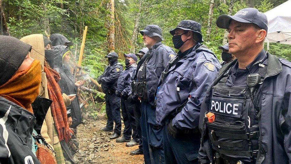 Des officiers de la GRC et des manifestants se font face.