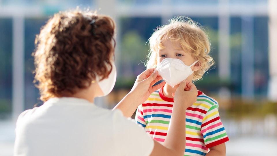 Une mère masquée installe un masque sur le visage de son fils.