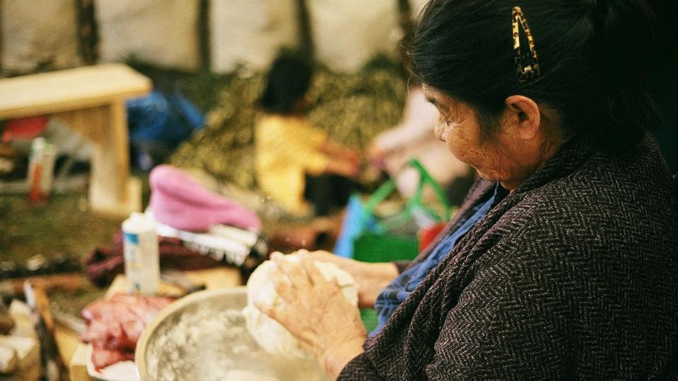 Une femme autochtone façonne une pâte à banique.