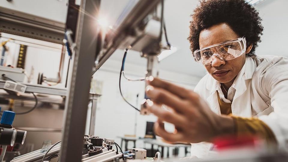 Une scientifique travaille sur un appareil technologique.