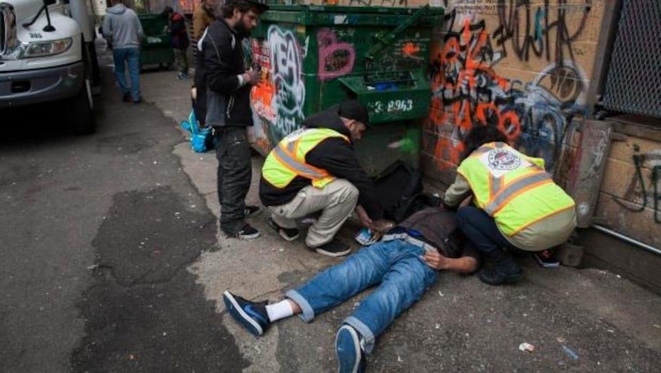 Des secouristes sont accroupis pour traiter un homme étendu au sol, sur le dos, dans une ruelle dont les murs sont couverts de graffiti.