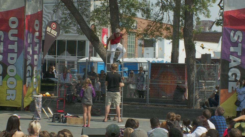 Un amuseur public monte dans une échelle pendant qu'un homme tient celle-ci en place.