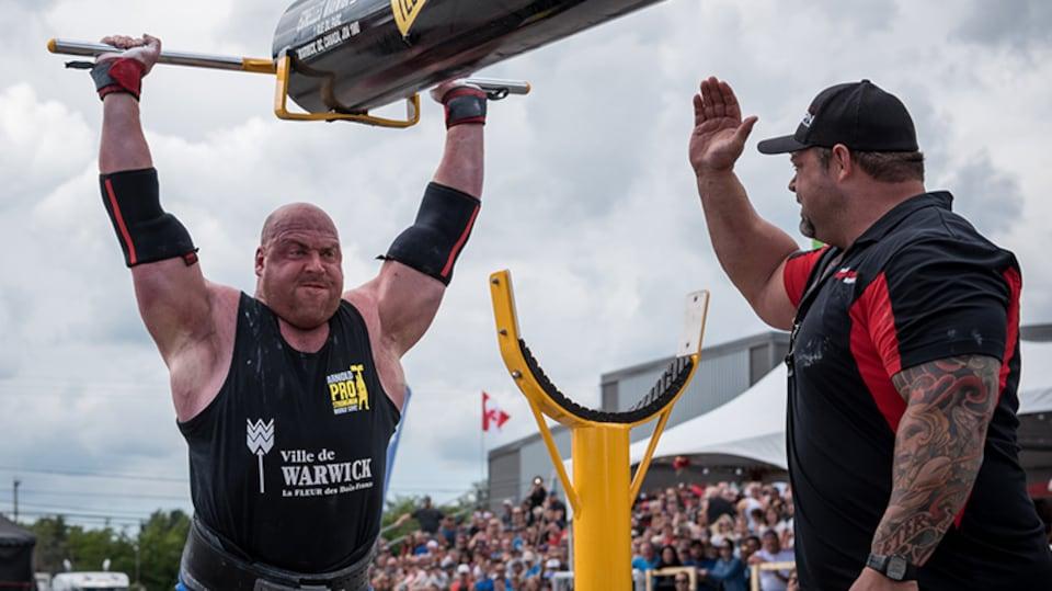 On voit un homme musclé qui soulève un objet très lourd sous les yeux d'un officiel de la compétition.