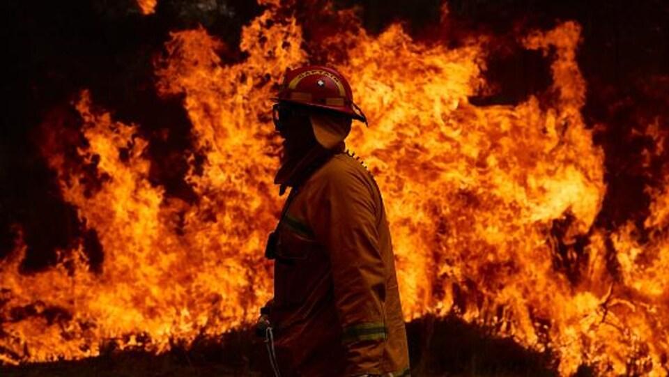 Avant-plan d'un pompier et un énorme brasier forestier en arrière-plan, à Sydney, en Australie.