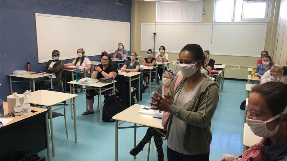 Des adultes portant un masque se désinfectent les mains dans une salle de classe.