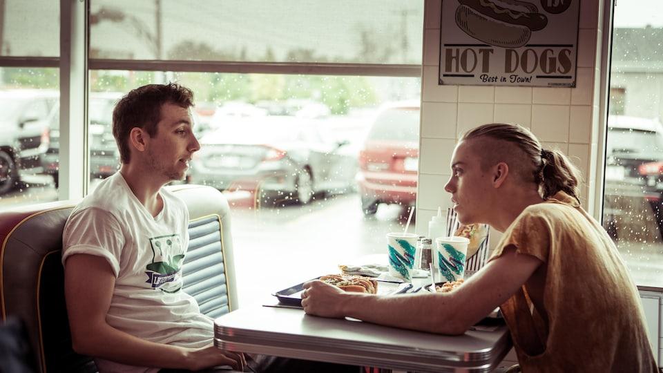 Les deux hommes sont assis l'un en face de l'autre dans un restaurant.