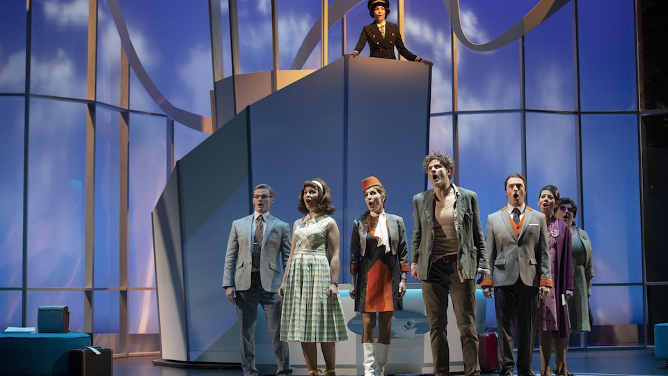 Huit chanteurs sur scène dans les décors de l'opéra Flight.