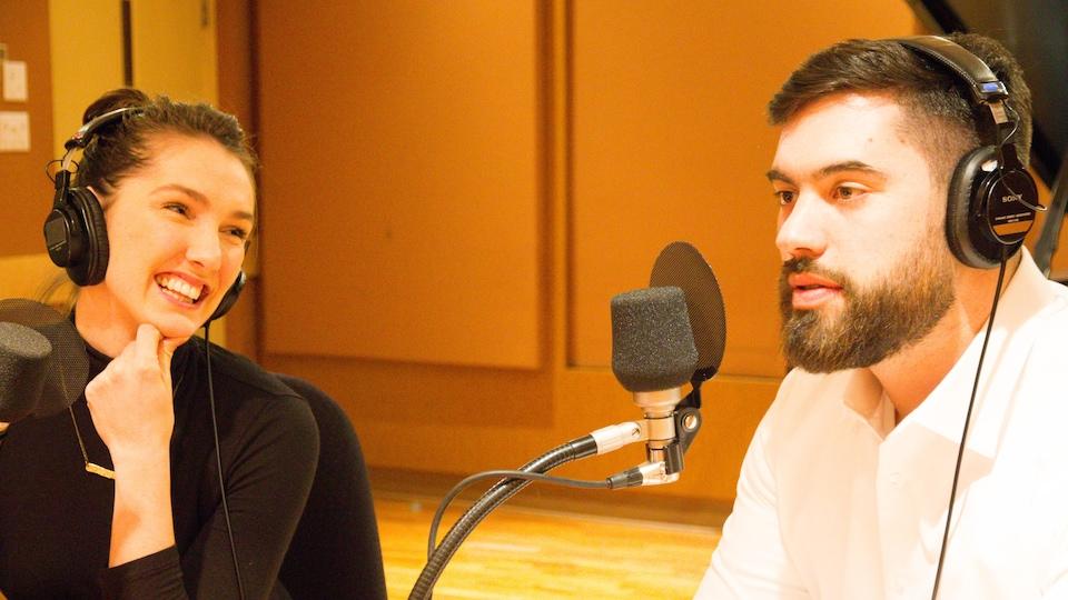 Une femme souriante regarde un homme qui s'exprime à un micro.