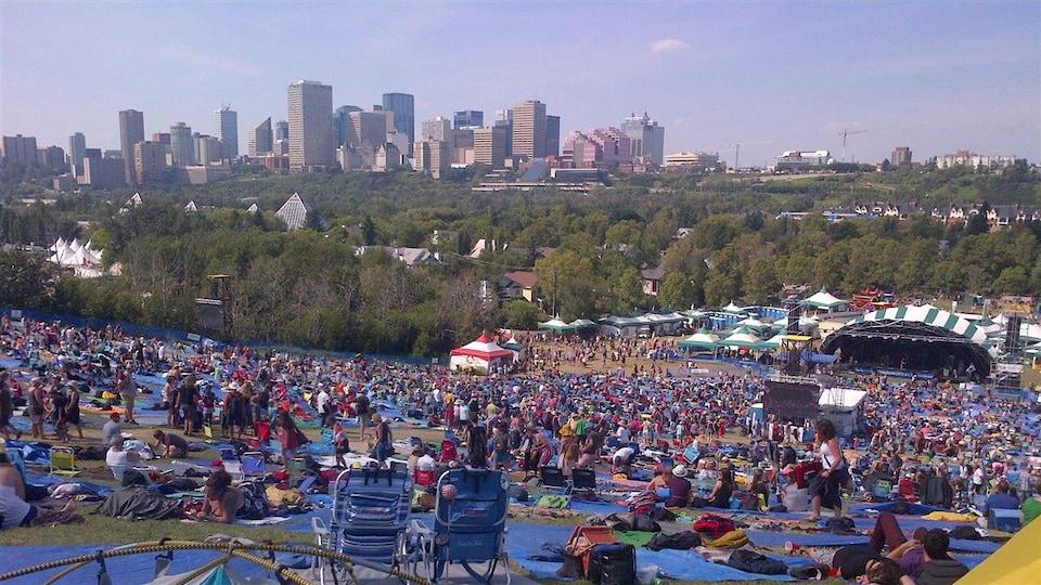 Des festivaliers dans un parc devant des scènes, avec vue sur le centre-ville.