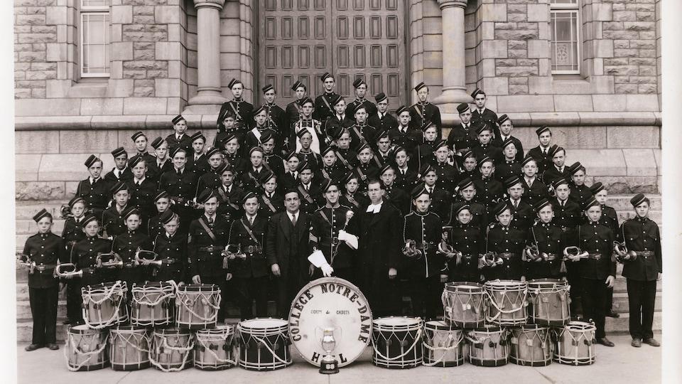 Un corps de tambour et clairons du Collège Notre-Dame à l'extérieur devant un édifice.