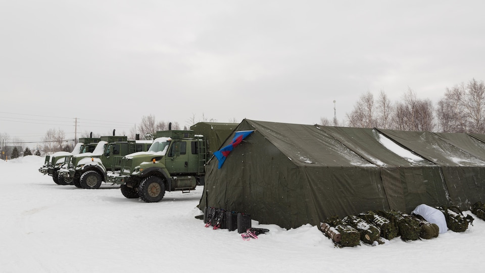 Un grande tente aux côtés de trois camions de l'armée canadienne.