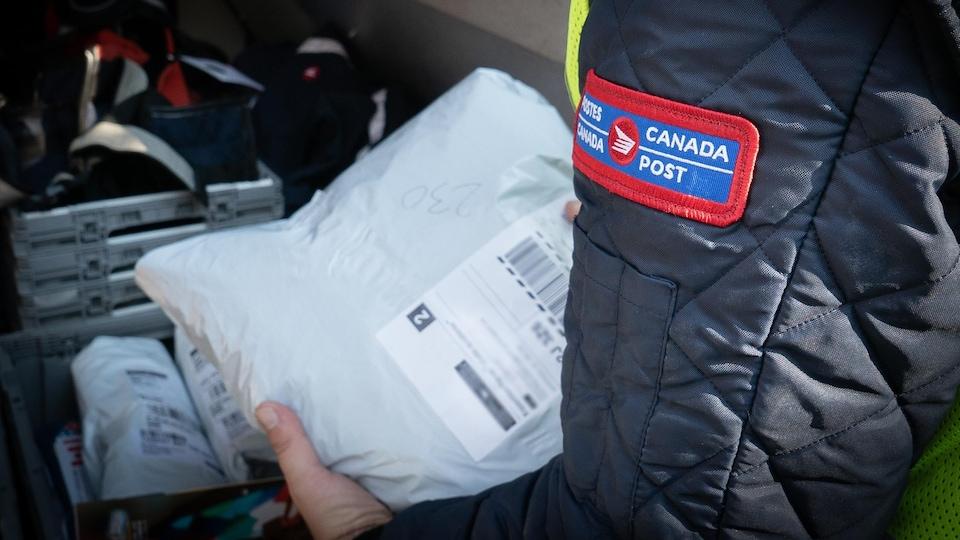 Gros plan sur un facteur de Postes Canada qui sort un colis blanc de son bac dans son camion.